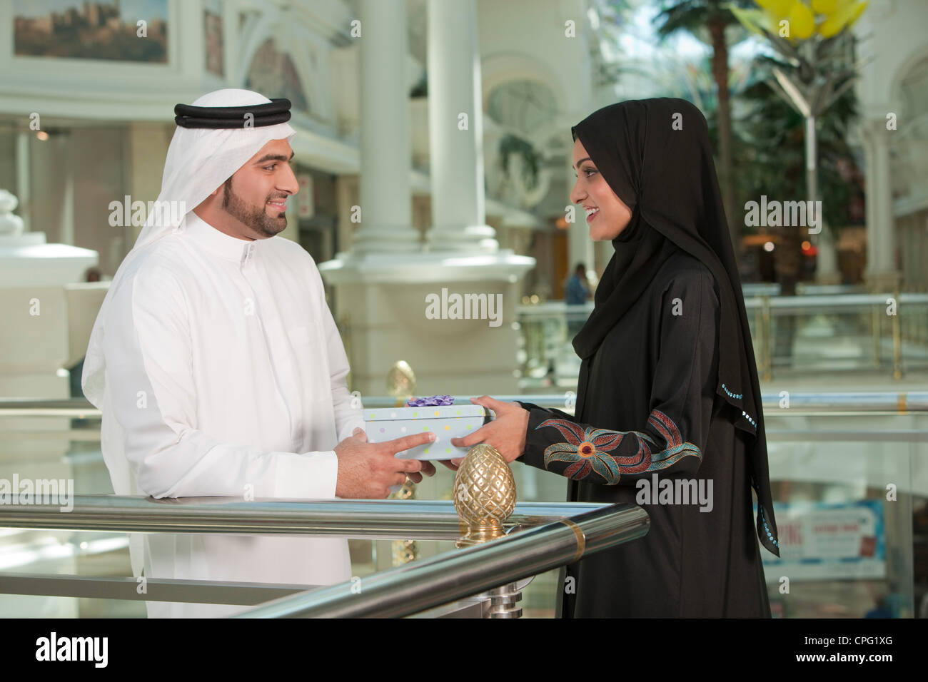 Arab man giving gift to woman. - Stock Image