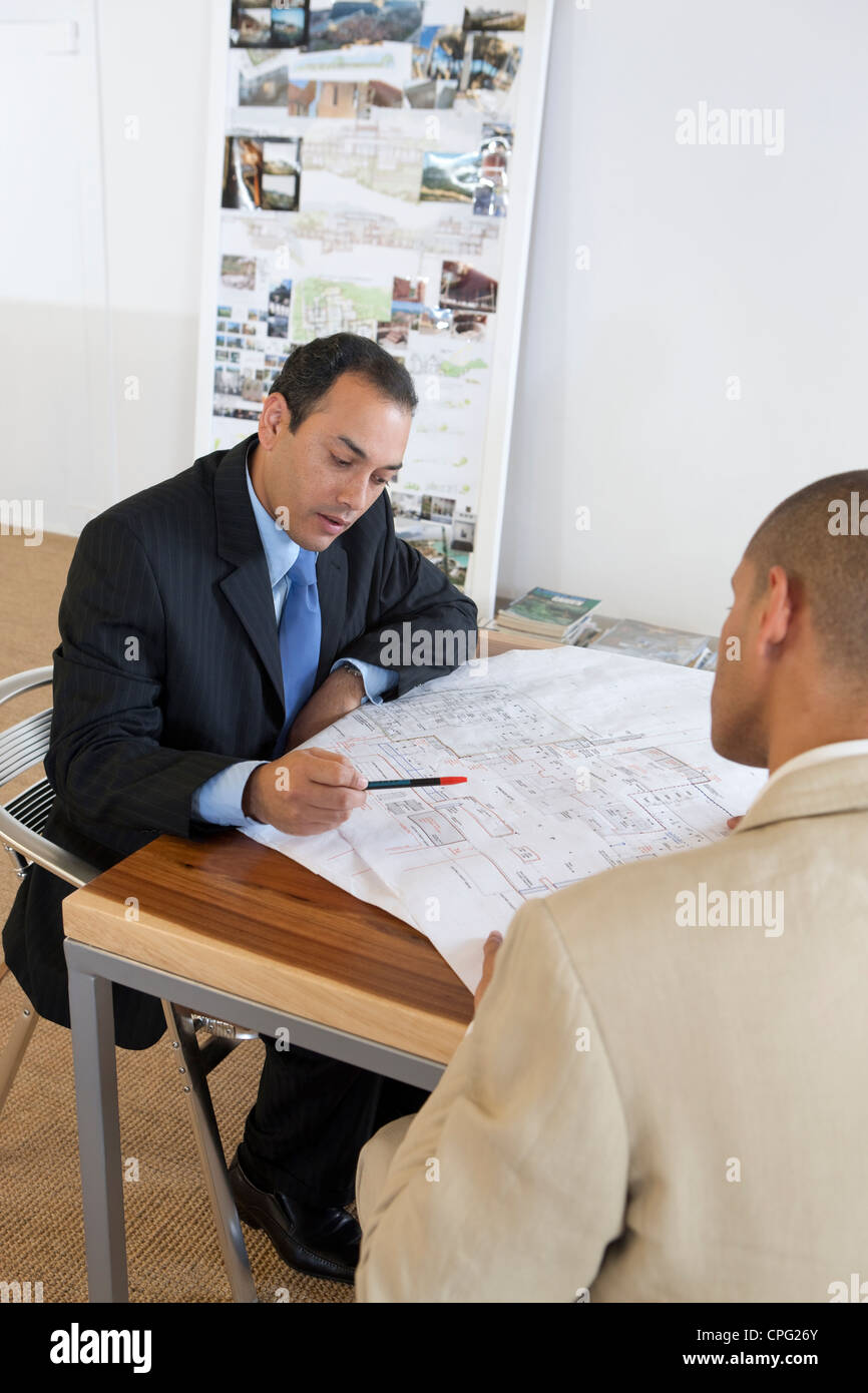 Two businessmen discussing over blueprint. - Stock Image