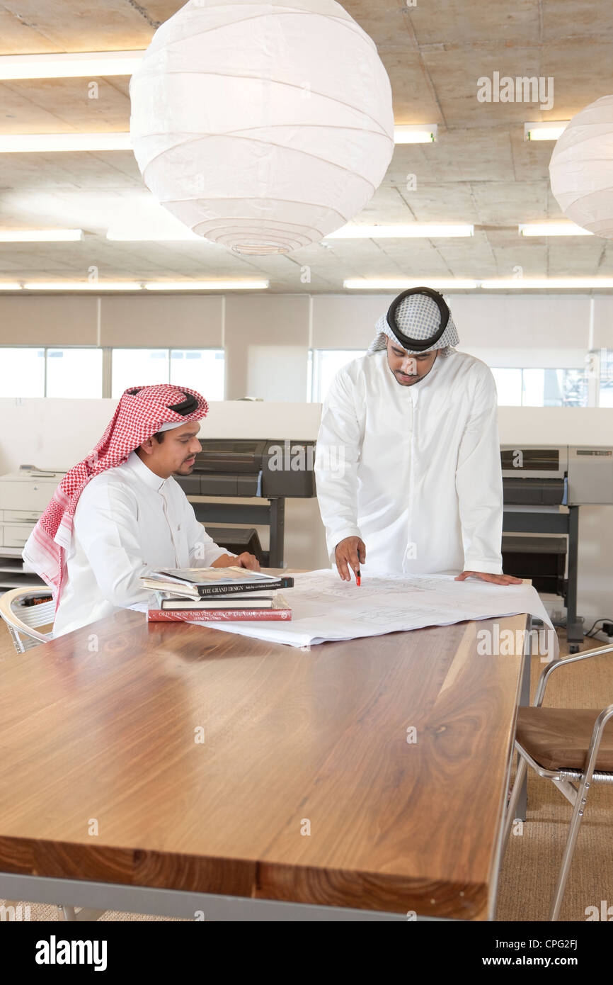 Two arab businessmen discussing over blueprint. Stock Photo