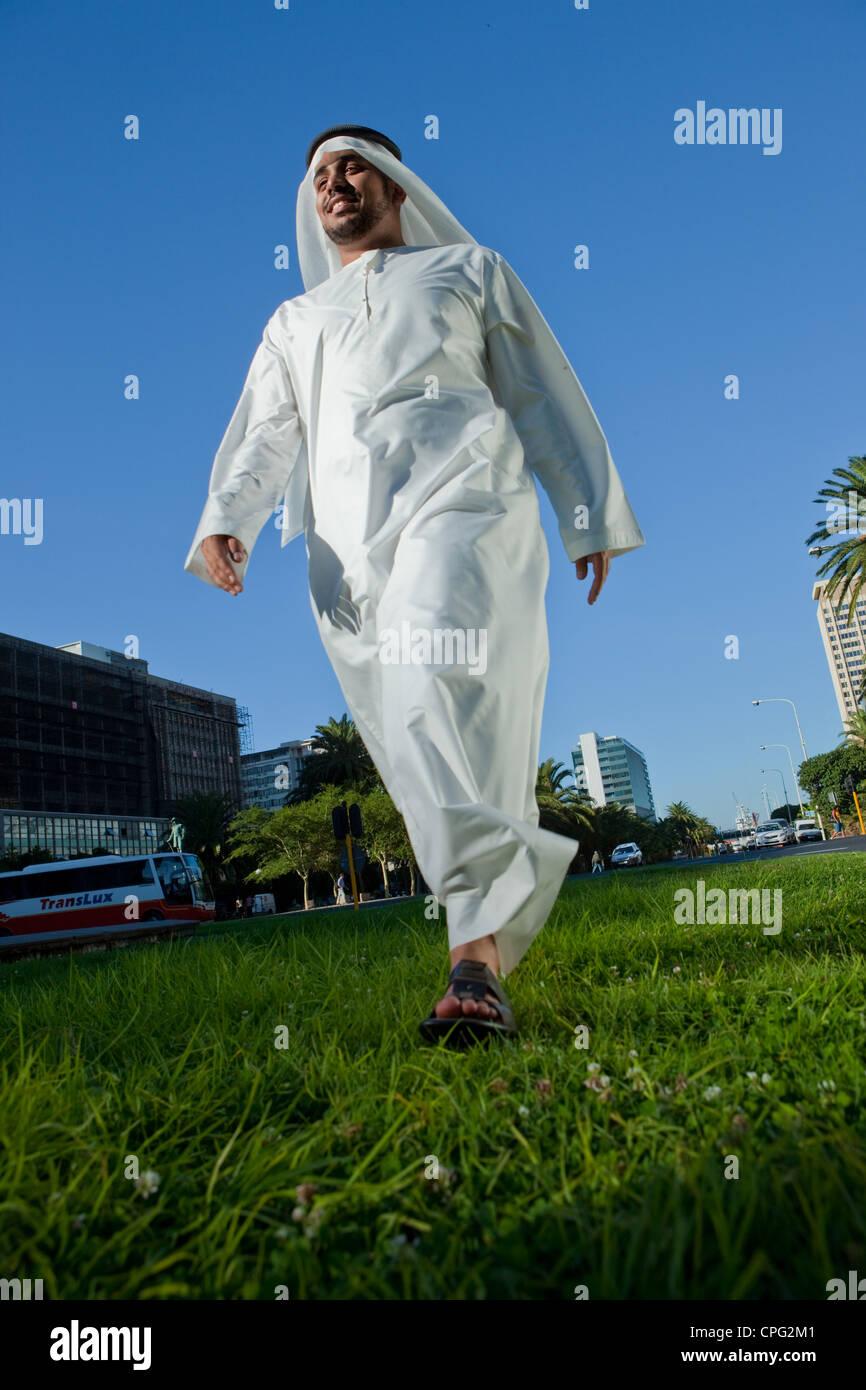 Arab man walking on street, smiling. Stock Photo