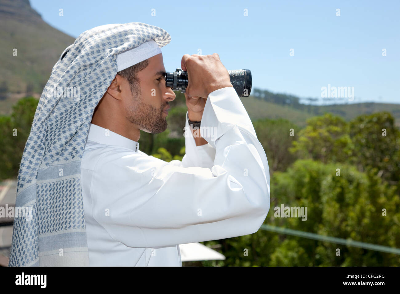 Arab man with binoculars, standing at the balcony. - Stock Image