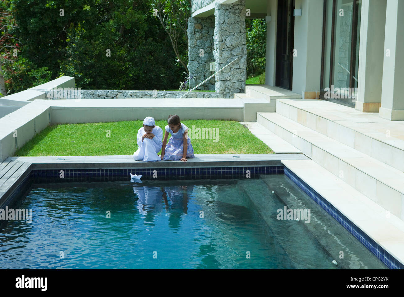 Boy and girl with paper boat by swimming pool. - Stock Image