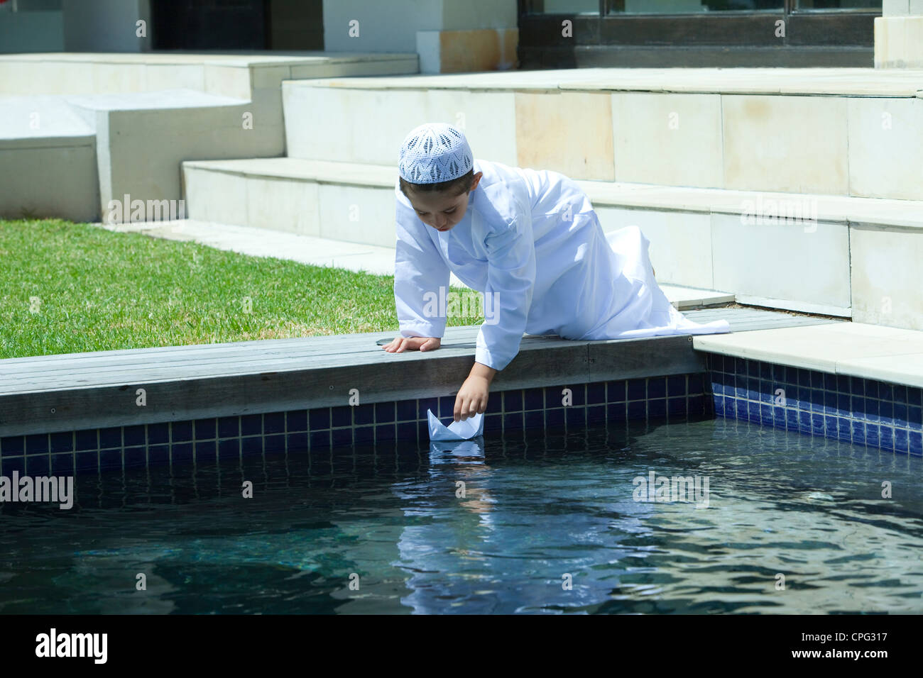 Arab boy playing paper boat by swimming pool. - Stock Image