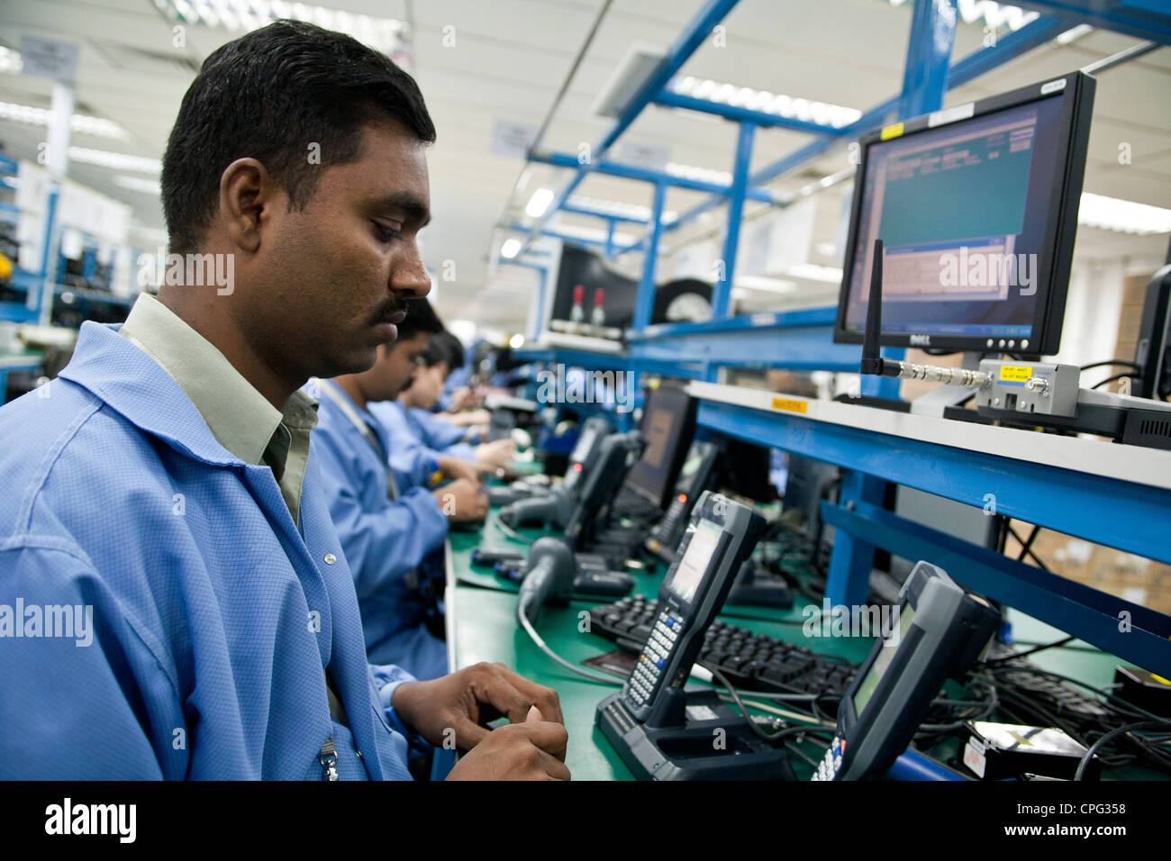 Workers test hand-held inventory computer devices on the assembly line at the Venture Corp. factory in Singapore - Stock Image