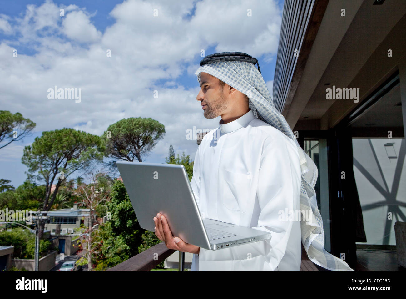 Arab man with laptop, standing by the balcony. - Stock Image