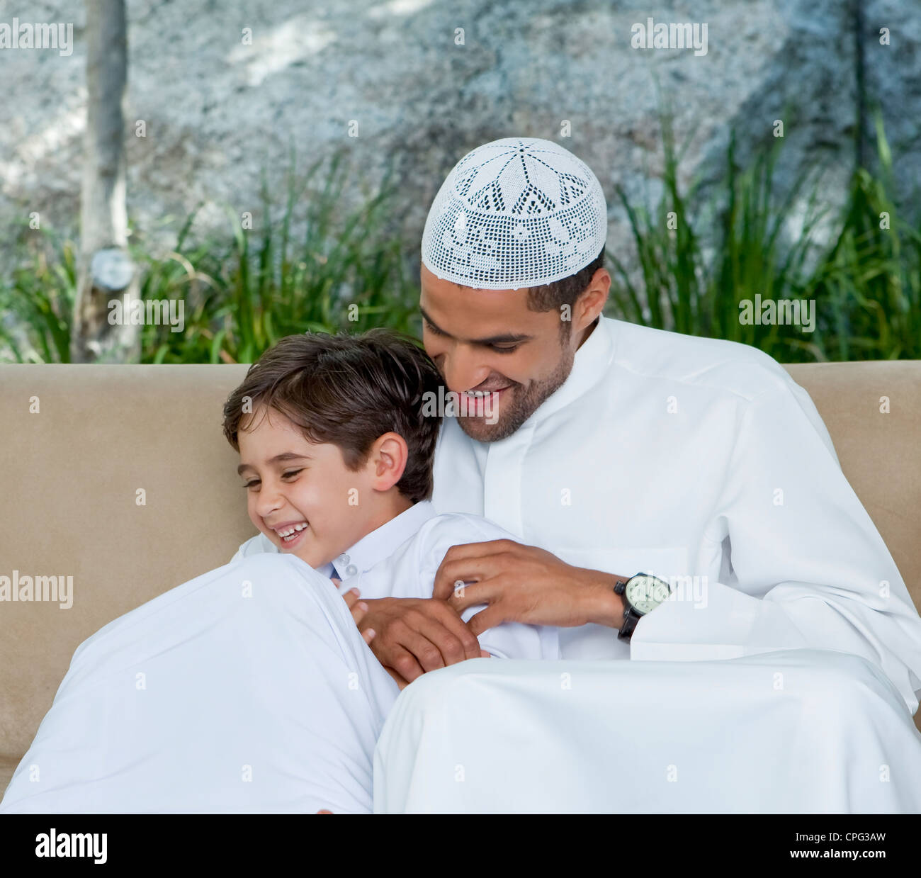 Arab father and son playing at the sofa. - Stock Image
