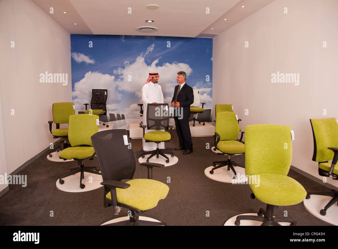 Salesman assisting arab man shopping for office chairs in furniture store. - Stock Image
