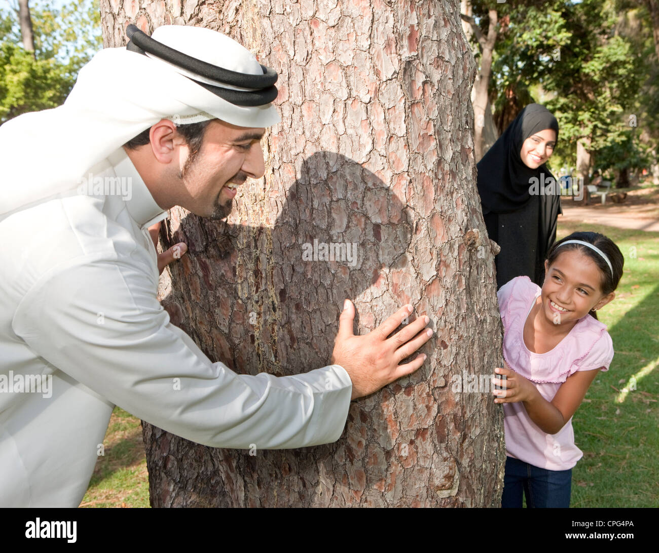 Arab family playing hide and seek in the park. - Stock Image