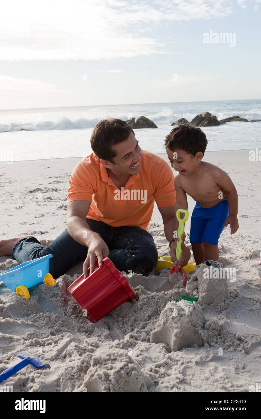 Father with son building sandcastles, smiling. - Stock Image