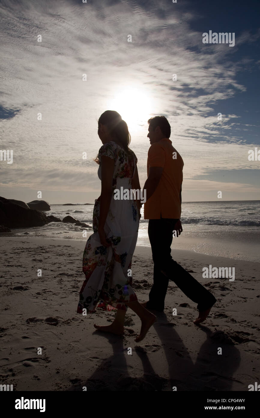 Couple holding hands and walking on beach. - Stock Image