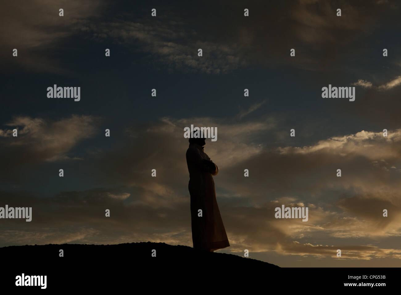 Arab man standing on top of rock, arms crossed. - Stock Image