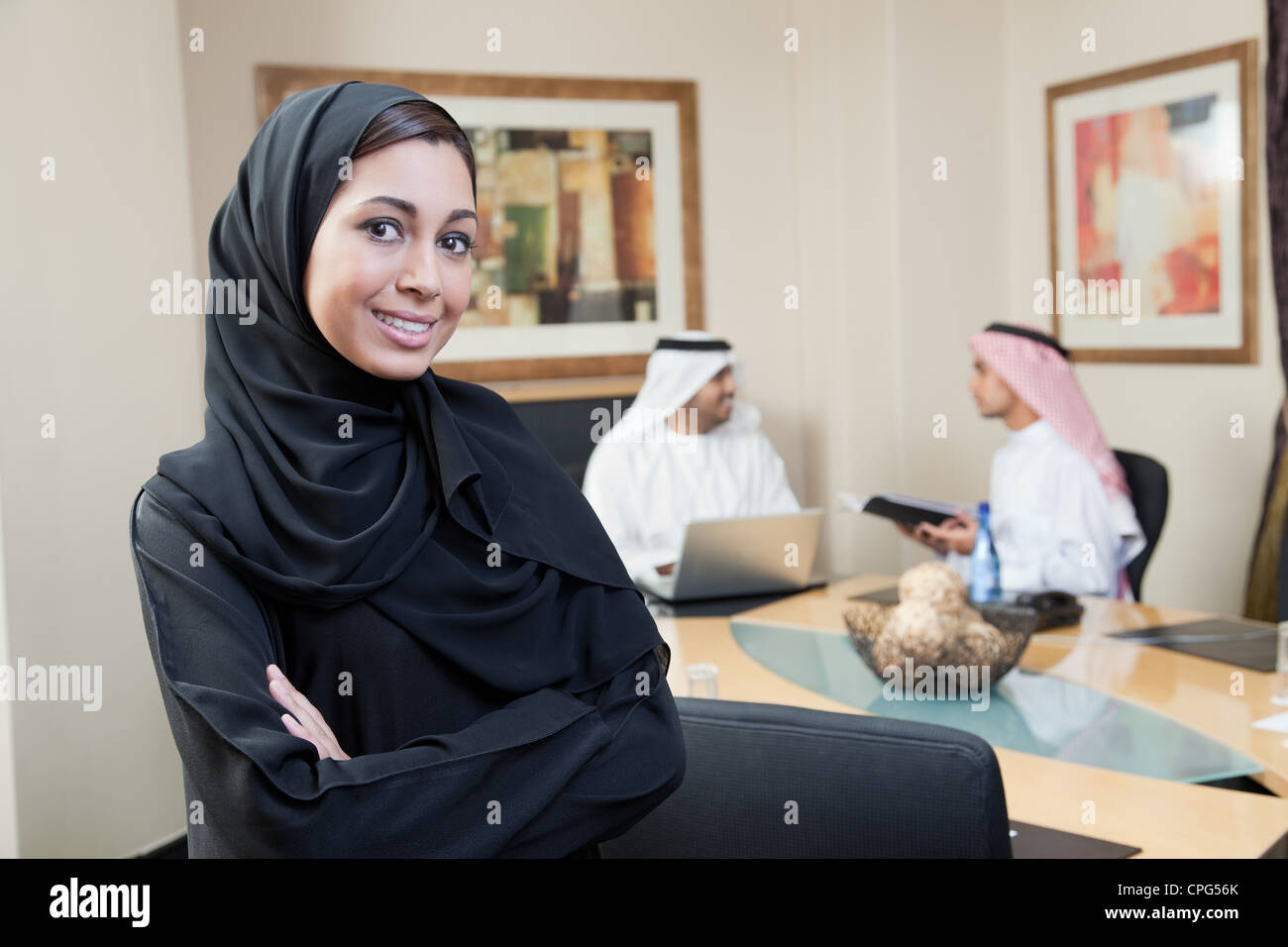 Arab businesswoman arms crossed, standing in meeting. - Stock Image