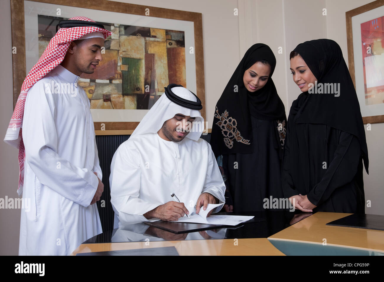 Arab businessman signing document, colleagues standing on the side. - Stock Image