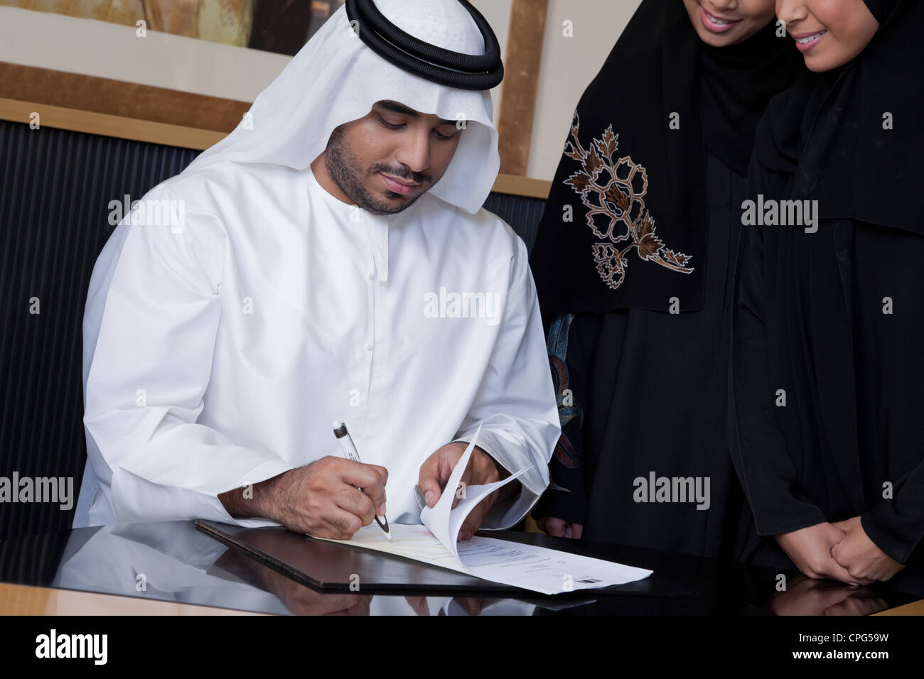 Arab businessman signing a document, businesswomen standing on the side. - Stock Image