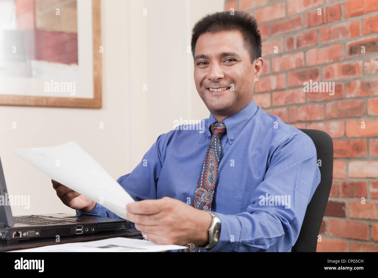 Businessman holding document at desk, smiling. - Stock Image