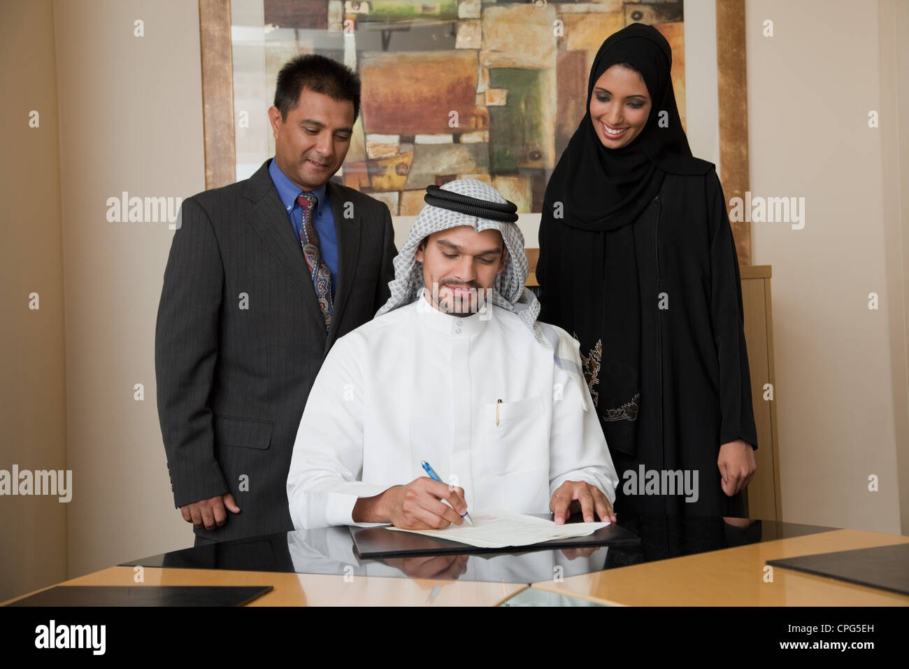 Arab businessman signing document, two colleague standing on the side. - Stock Image