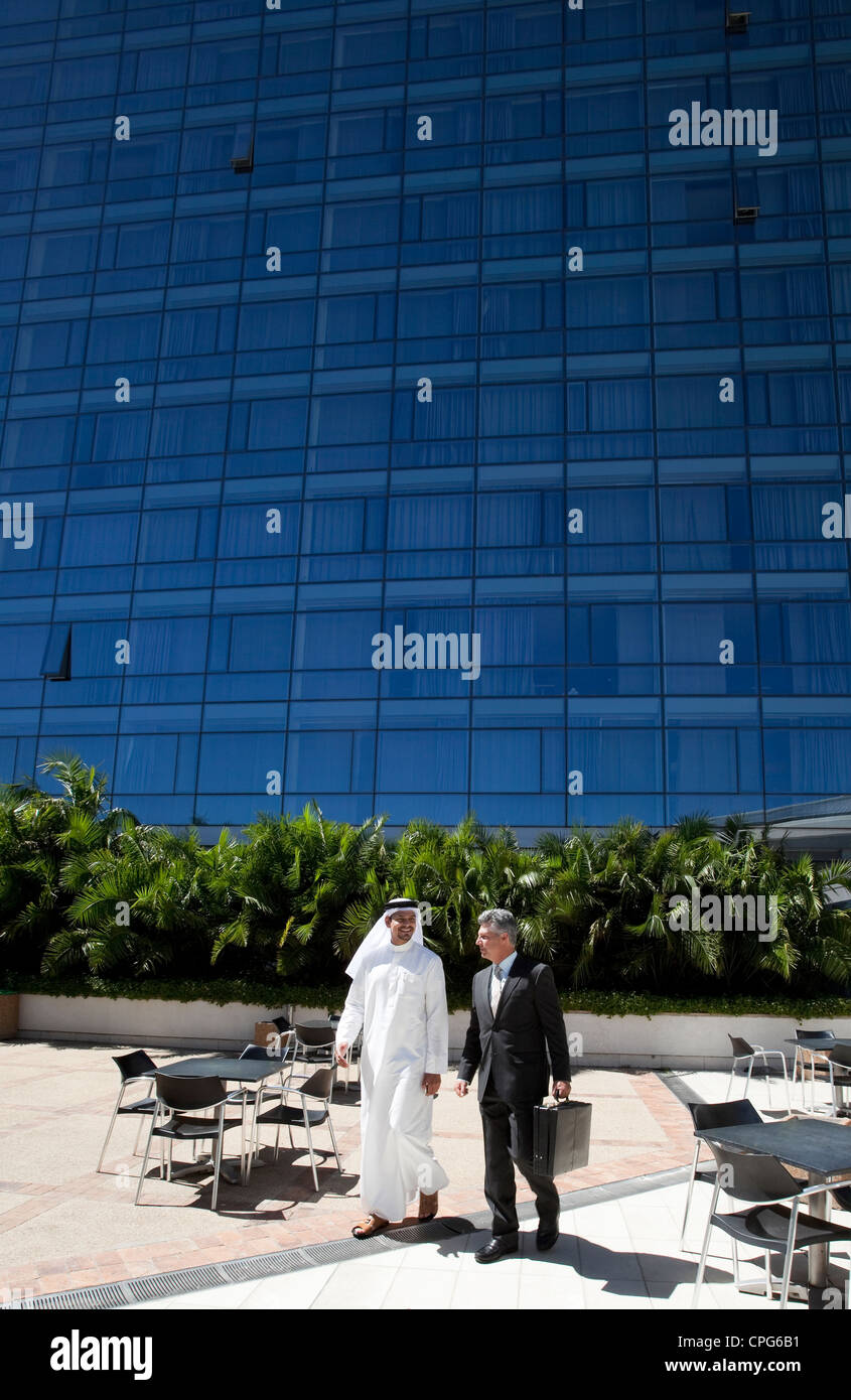 Arab businessman and western businessman walking in front of office building. - Stock Image