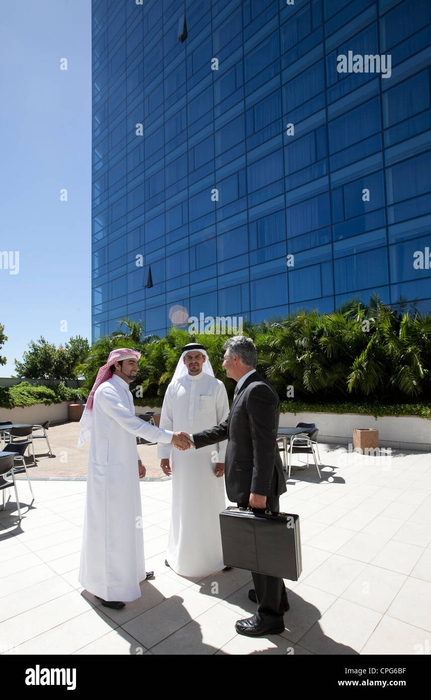 Three businessmen shaking hands in front of building. - Stock Image