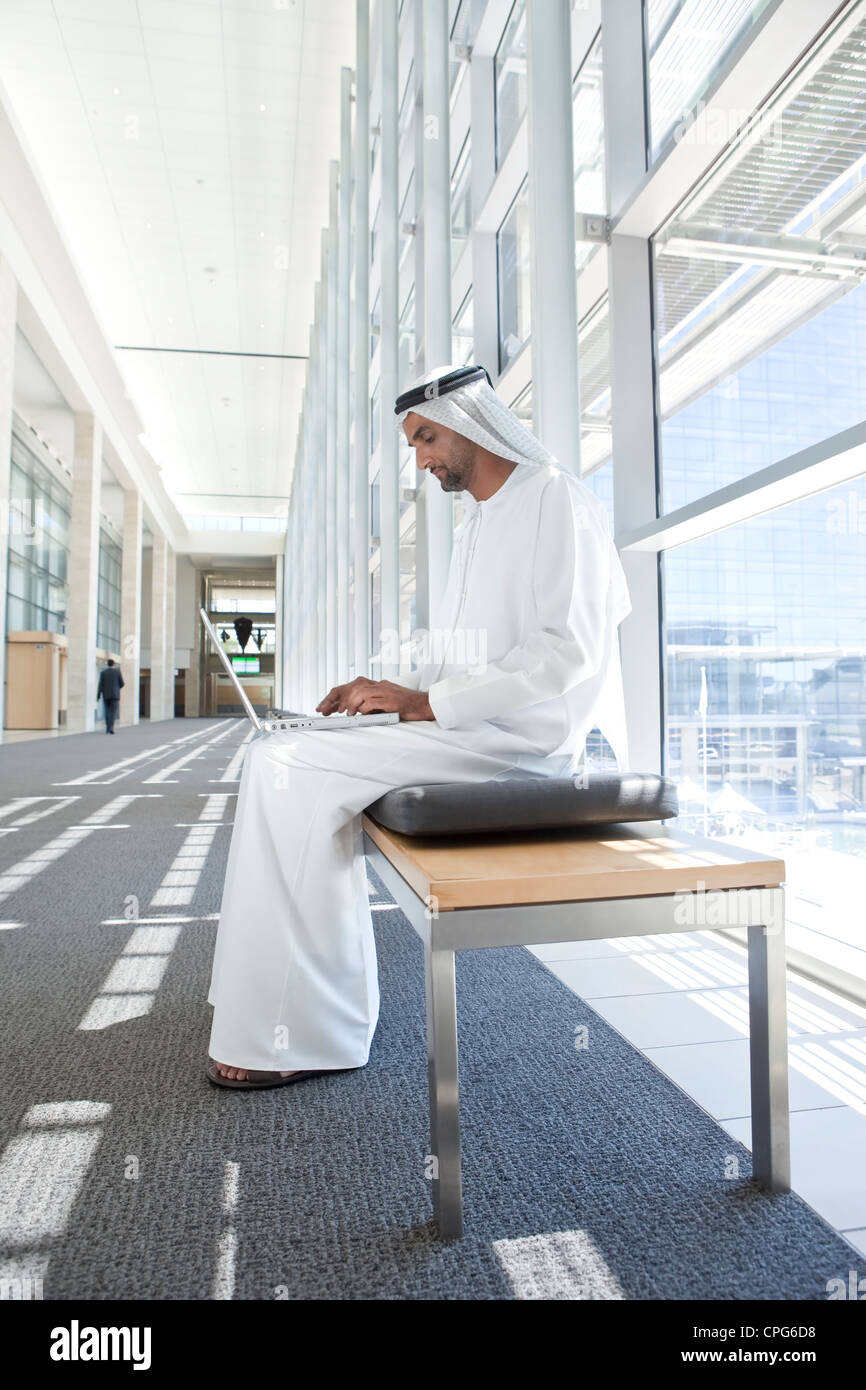 Arab businessman with laptop, sitting on bench on office hallway. - Stock Image