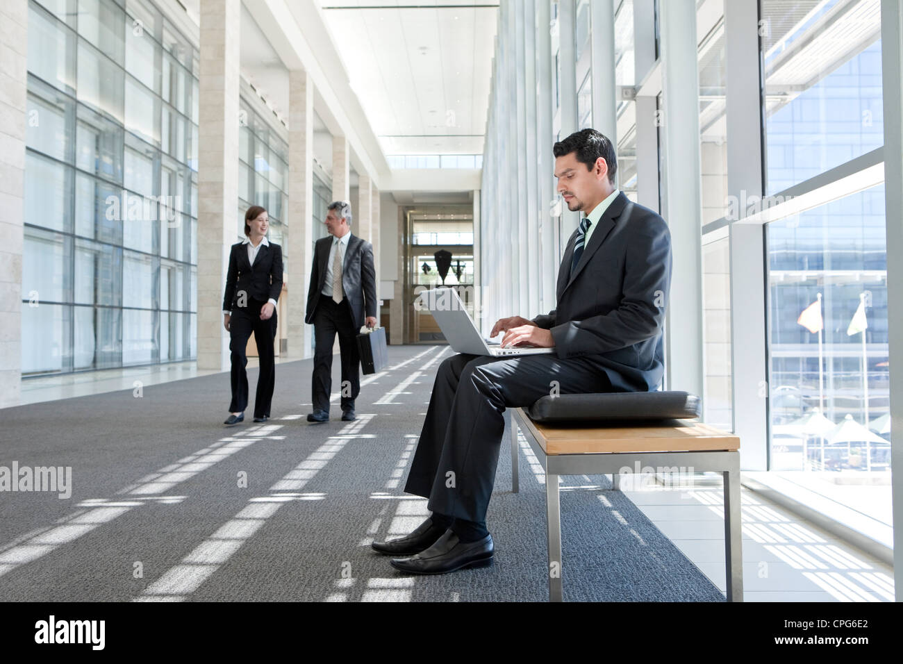 Businessman with laptop sitting on bench in office hallway, two business people talking by outdoor. - Stock Image