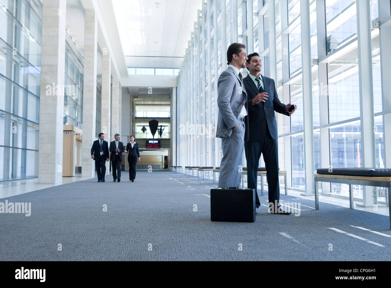 Two businessmen talking in office hallway. Three business people walking in background. - Stock Image