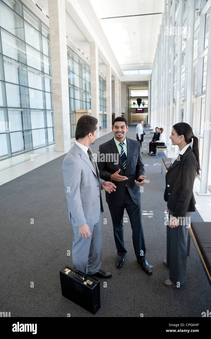 Three business people talking in the office hallway. - Stock Image