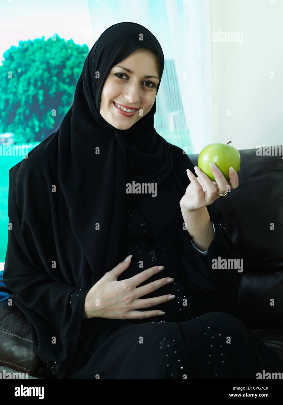 a pregnant arab mother sitting on the sofa with apple stock photo