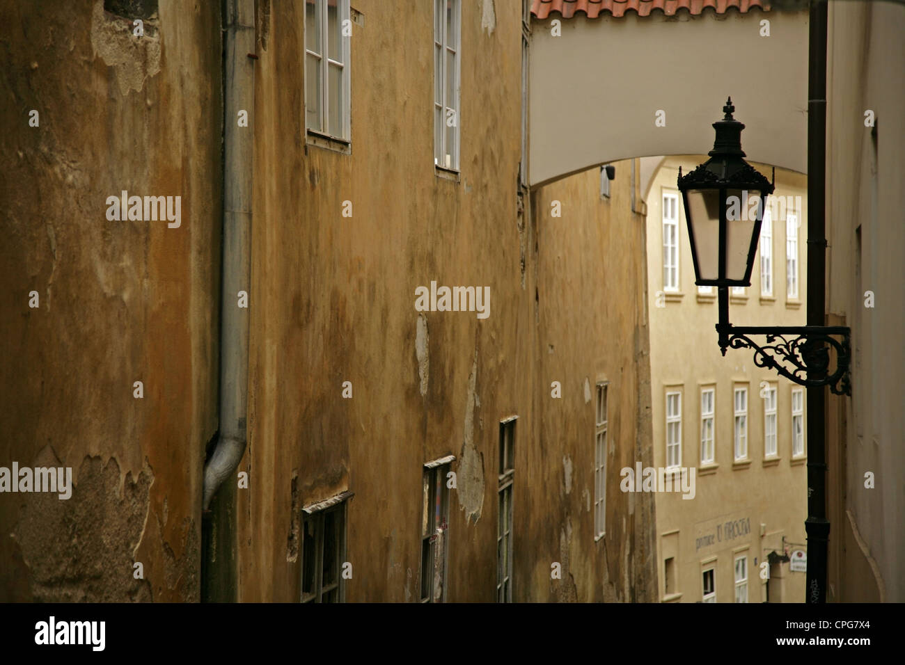 Old wrought iron streetlamp in narrow sidestreet, Prague, Czech Republic. - Stock Image