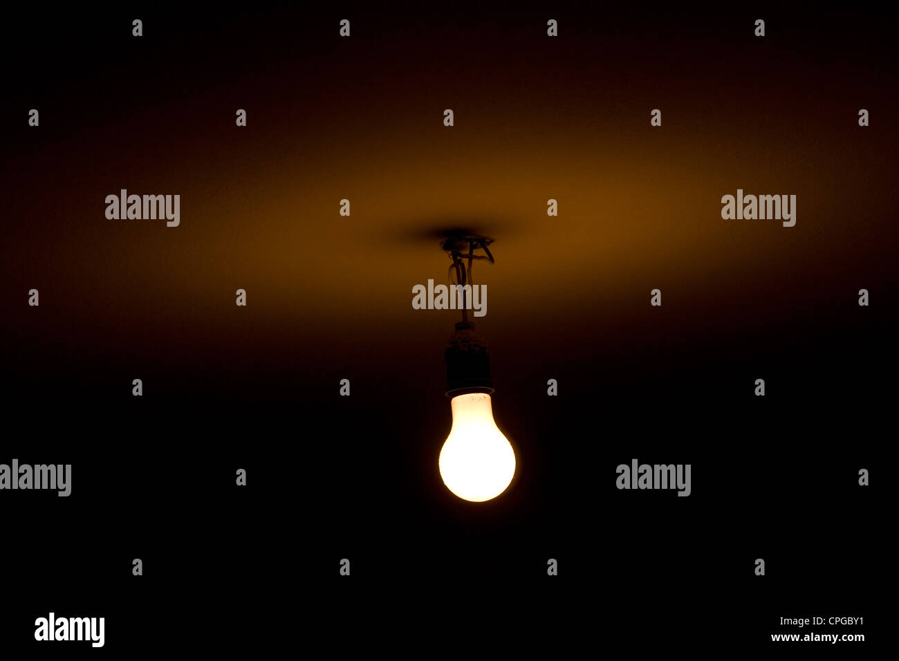 Bare light bulb hanging from the ceiling - Stock Image