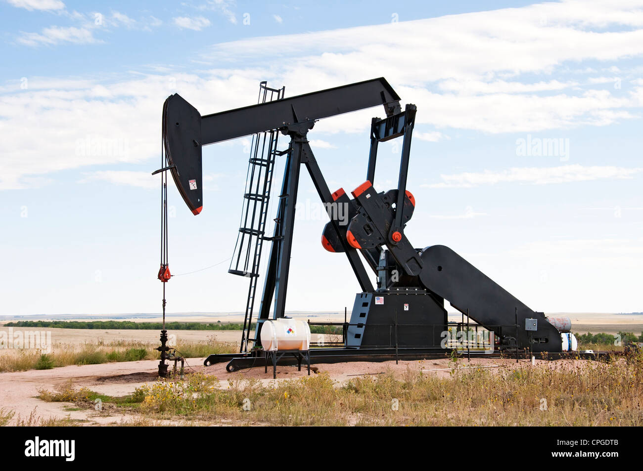 Pump jack starting the lifting stroke to brink crude oil up out of a producing oil well. - Stock Image