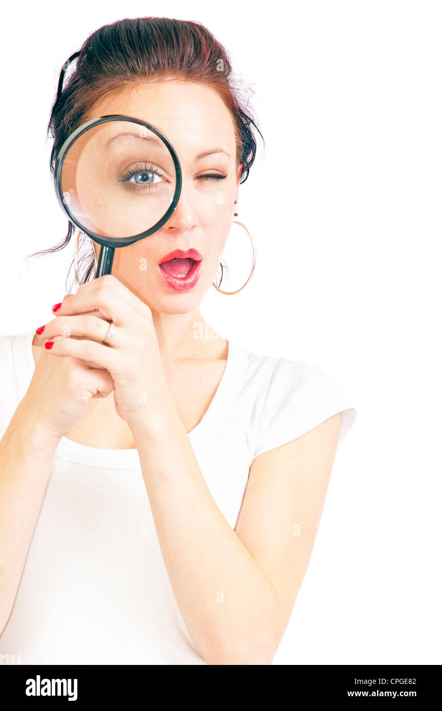 Attractive young woman looking through a magnifying glass isolated on a white background. - Stock Image