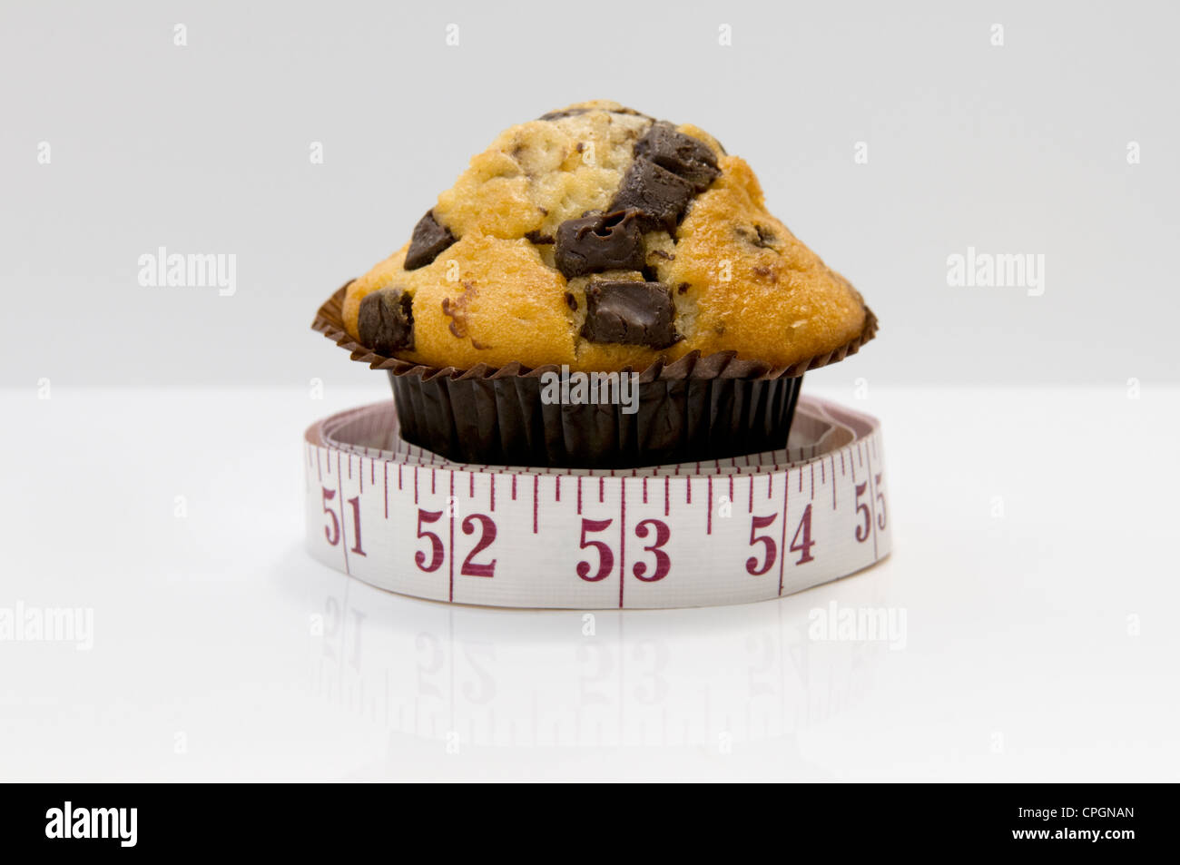 Chocolate chip muffin with tape measure depicting concept that eating cakes will pile on the inches - Stock Image