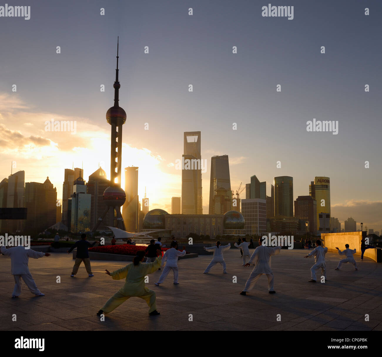 Tai Chi group exercising facing the sunrise and the Pudong high rise towers from The Bund Shanghai China - Stock Image