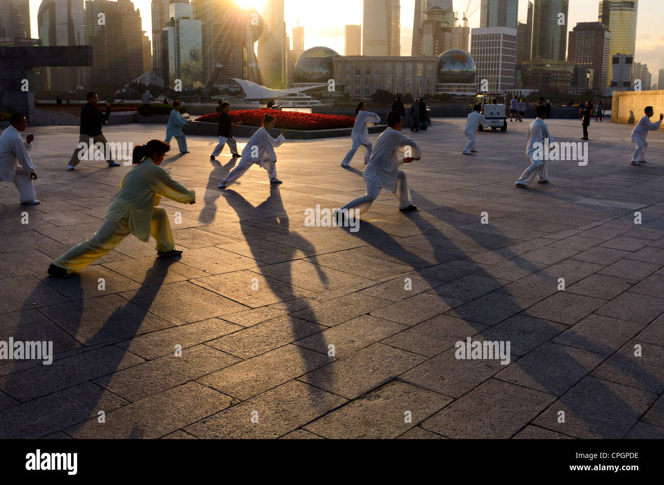 Long shadows of group doing Tai Chi exercises on the Bund at dawn with Shanghai skyline China - Stock Image