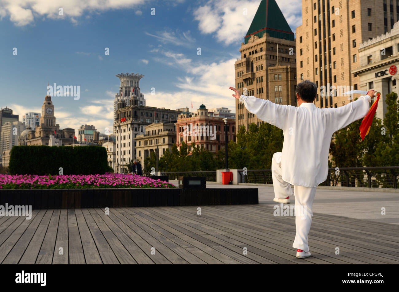 Man in white with Tai Chi sword exercising on the Bund at dawn in Shanghai China - Stock Image