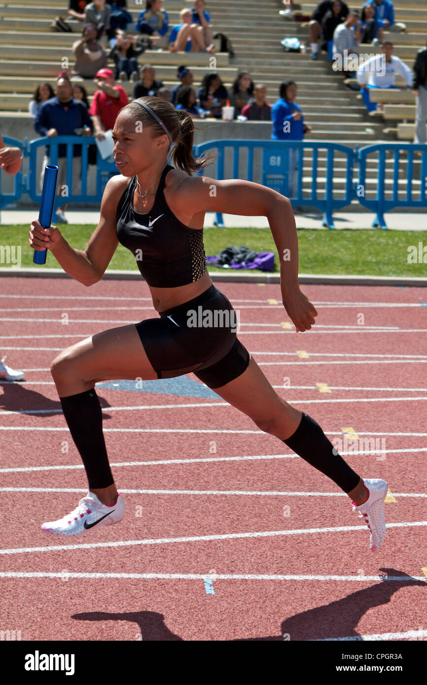 American Sprinter Allyson Felix with baton in hand running in a relay race at a  track and field meet in Drake Stadium - Stock Image