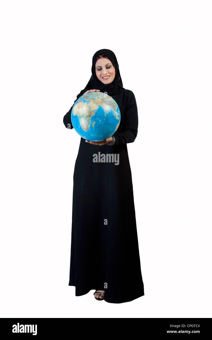 Arab woman holding a globe - Stock Image