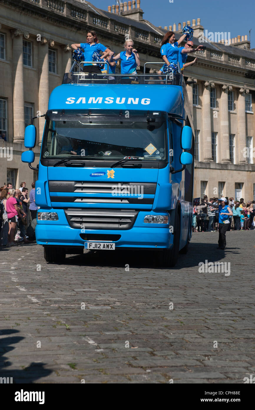 A Samsung sponsorship bus arrives in Bath's Royal Crescent ahead of the arrival of the Olympic torch relay procession. - Stock Image