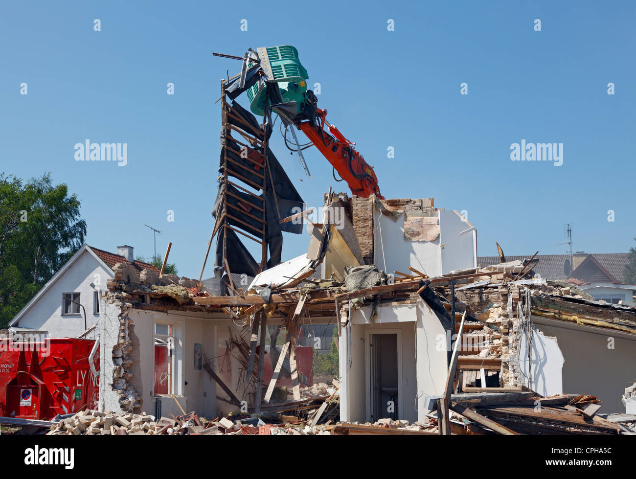 A house is demolished by use of a dredger to make space for a new supermarket, Denmark - Stock Image