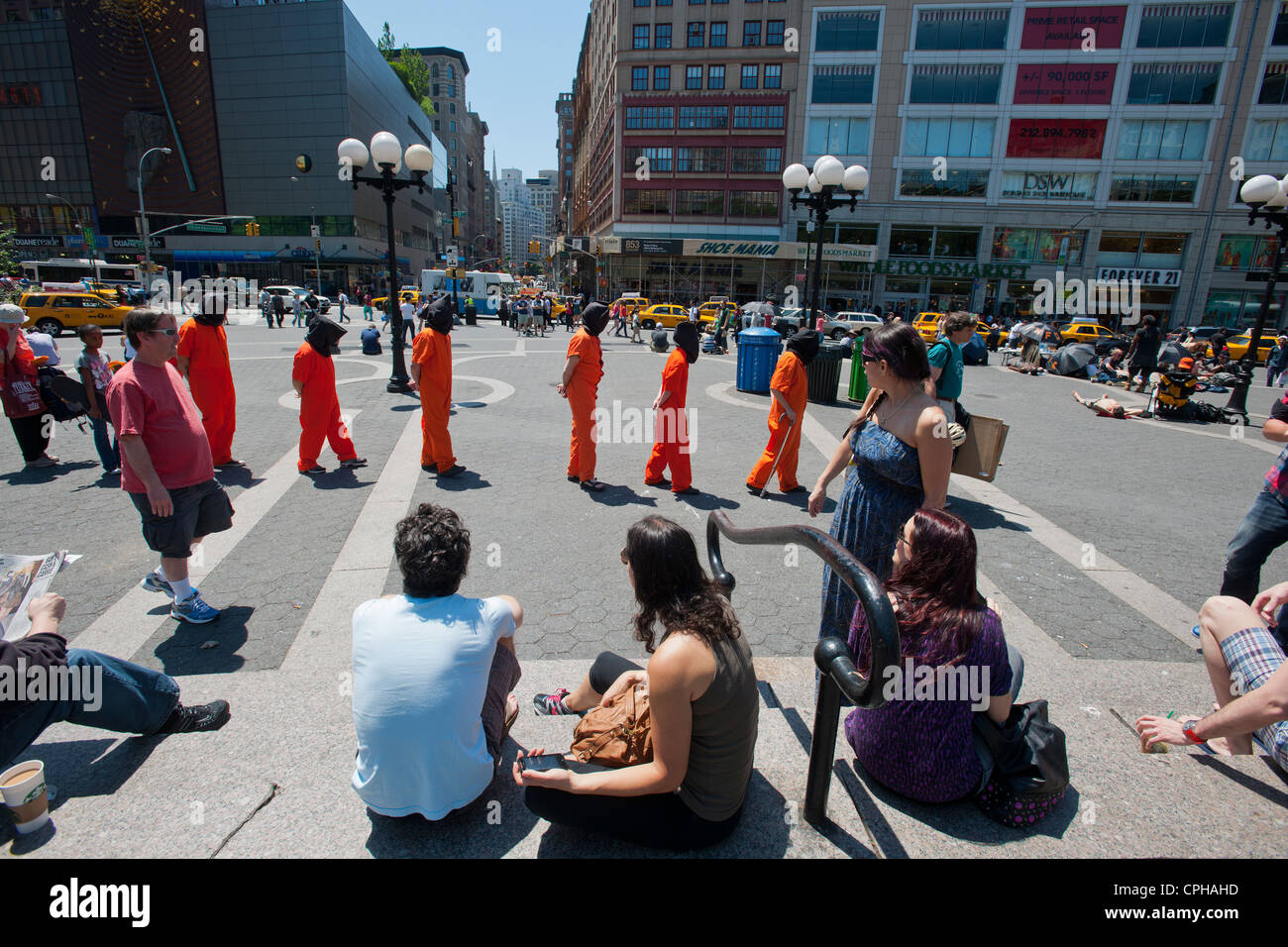 Volunteers from Witness Torture dress up as Guantanamo Bay detainees in Union Square Park in New York - Stock Image
