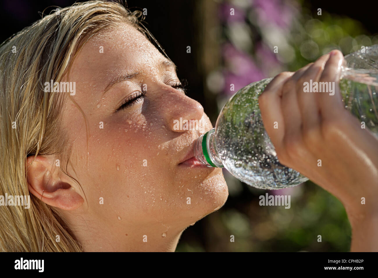 Pretty young girl drinking water - Stock Image