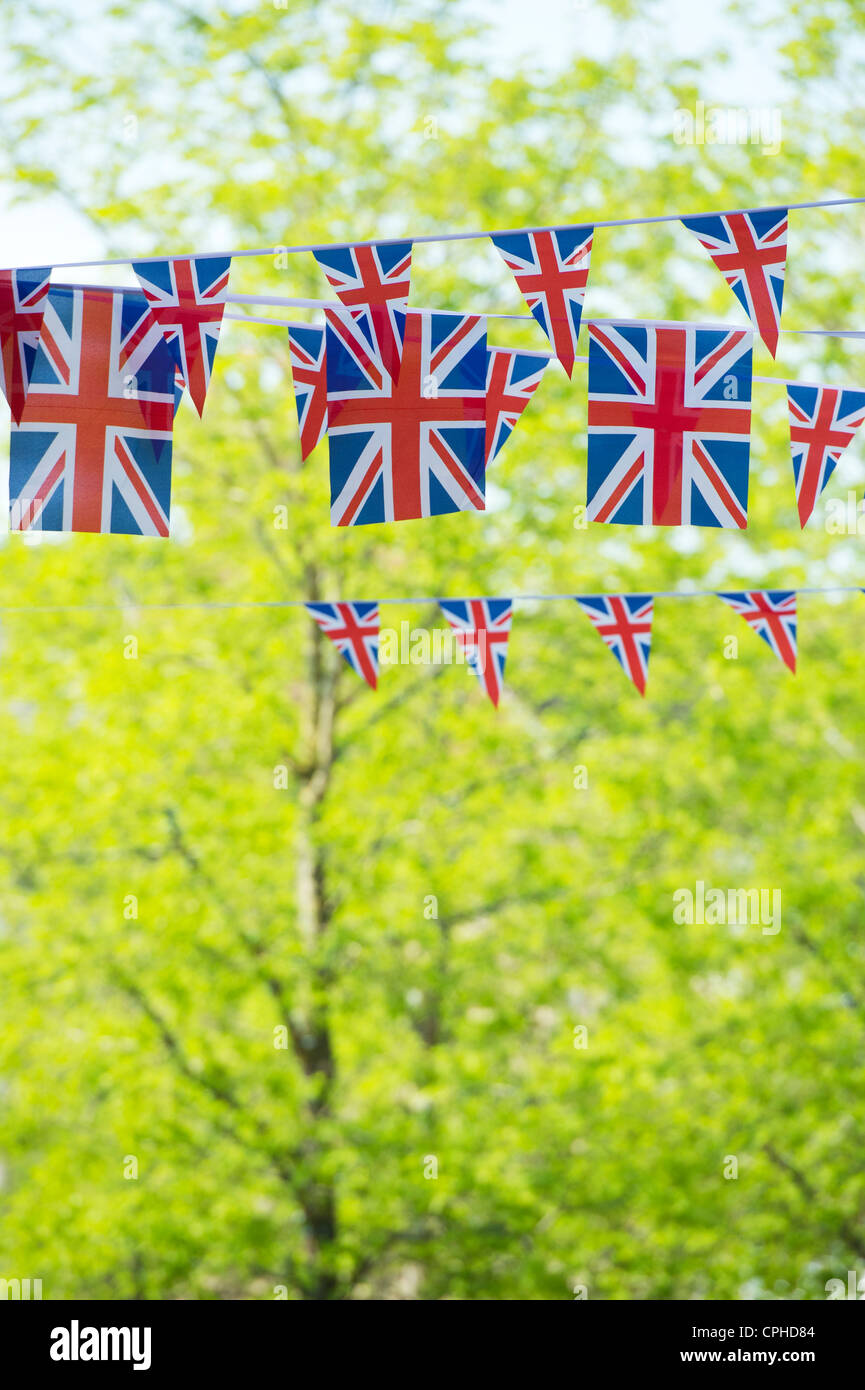 Union Jack flag bunting in front of sunlit trees - Stock Image