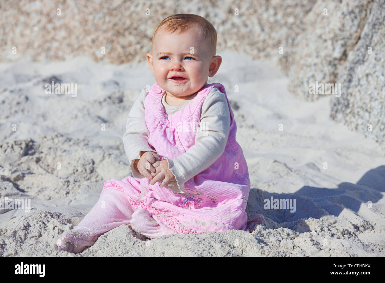 Young 8 month old baby girl on the beach smiling stock image