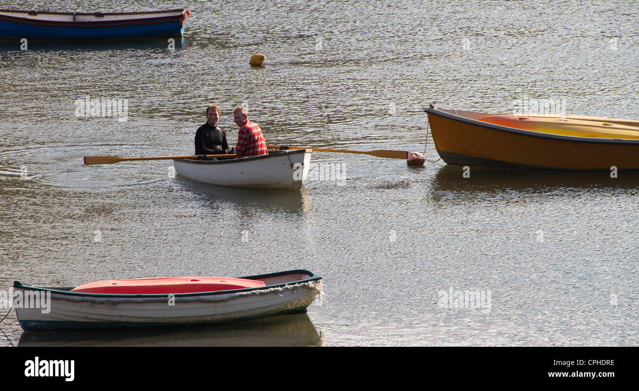 Two men in a rowing boat. - Stock Image