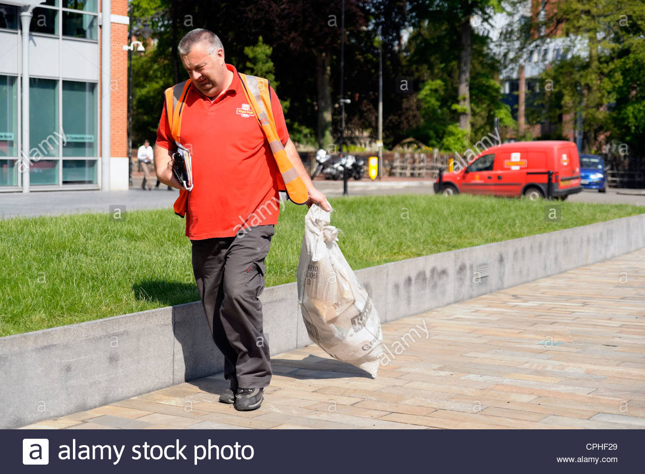 Postman carrying a sack of letters in Reading, Berkshire, UK. Royal Mail delivery man. - Stock Image