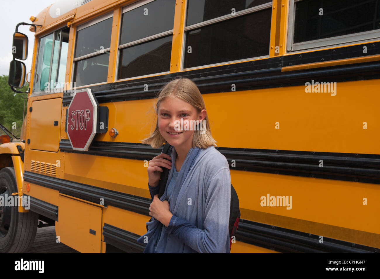 Middle school student smiling in front of her school bus. - Stock Image