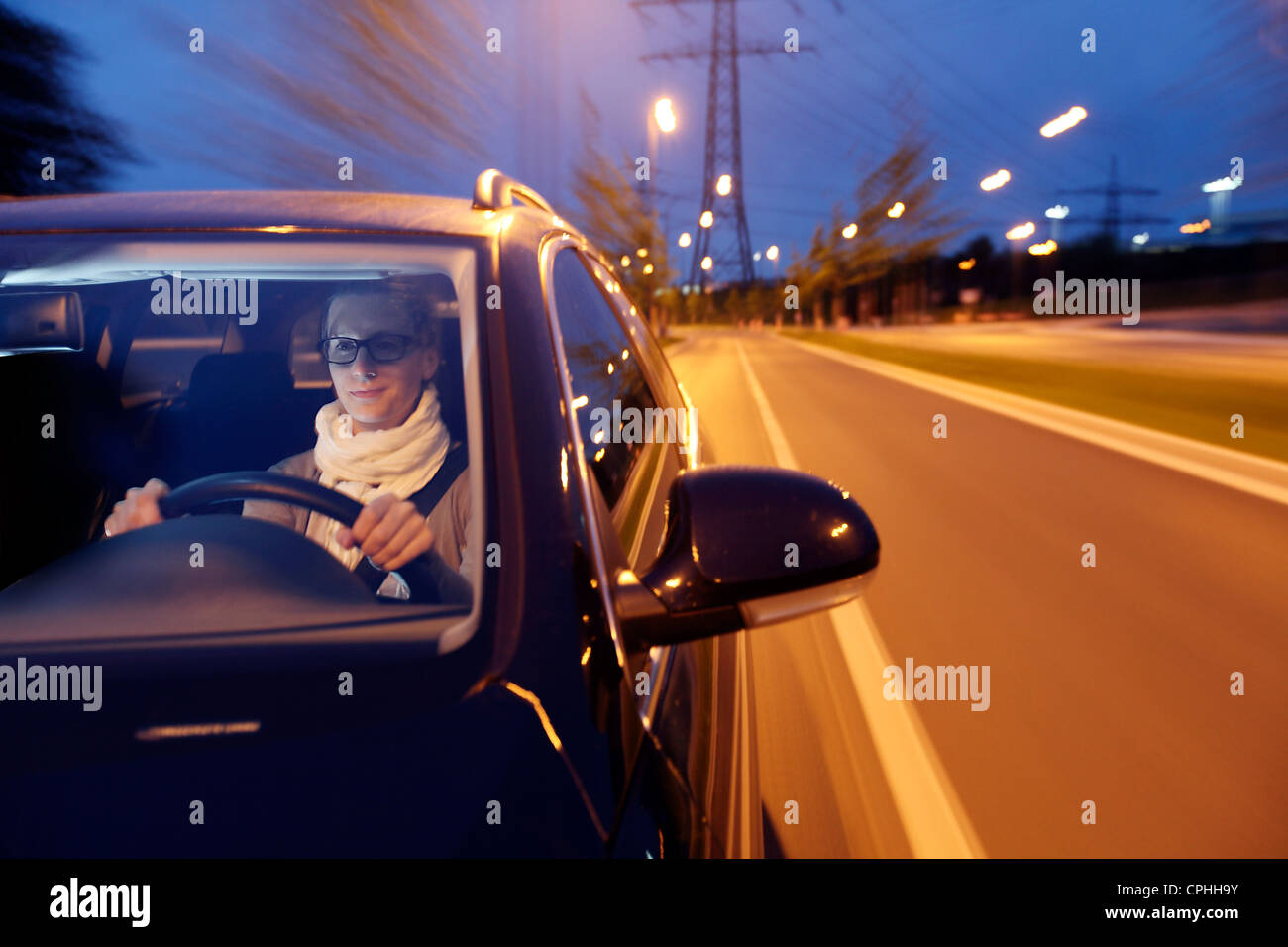 Young woman is driving a car at night, through a city, illuminated with streetlights. - Stock Image