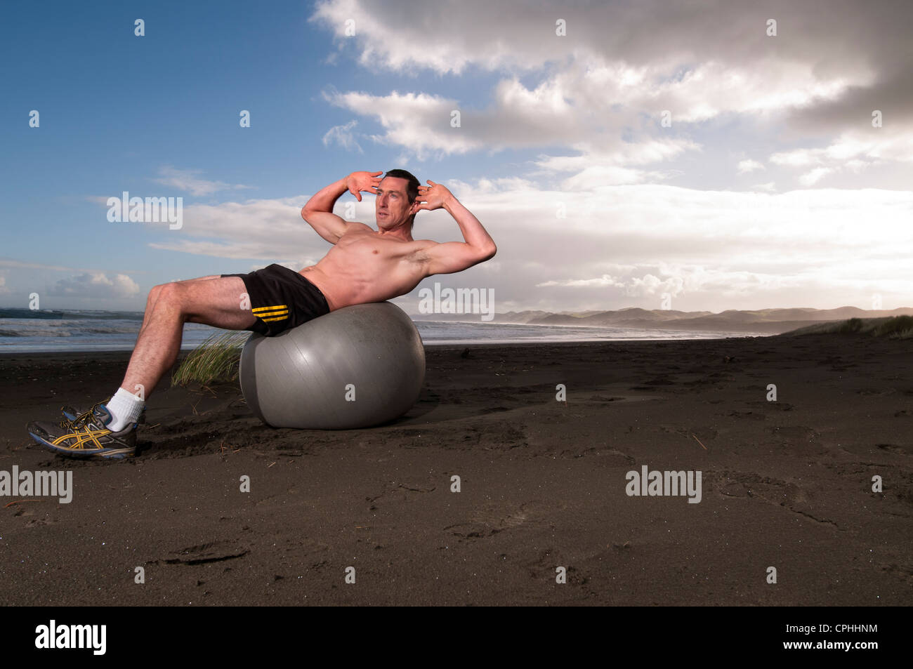 Man training on beach with exercise ball - Stock Image