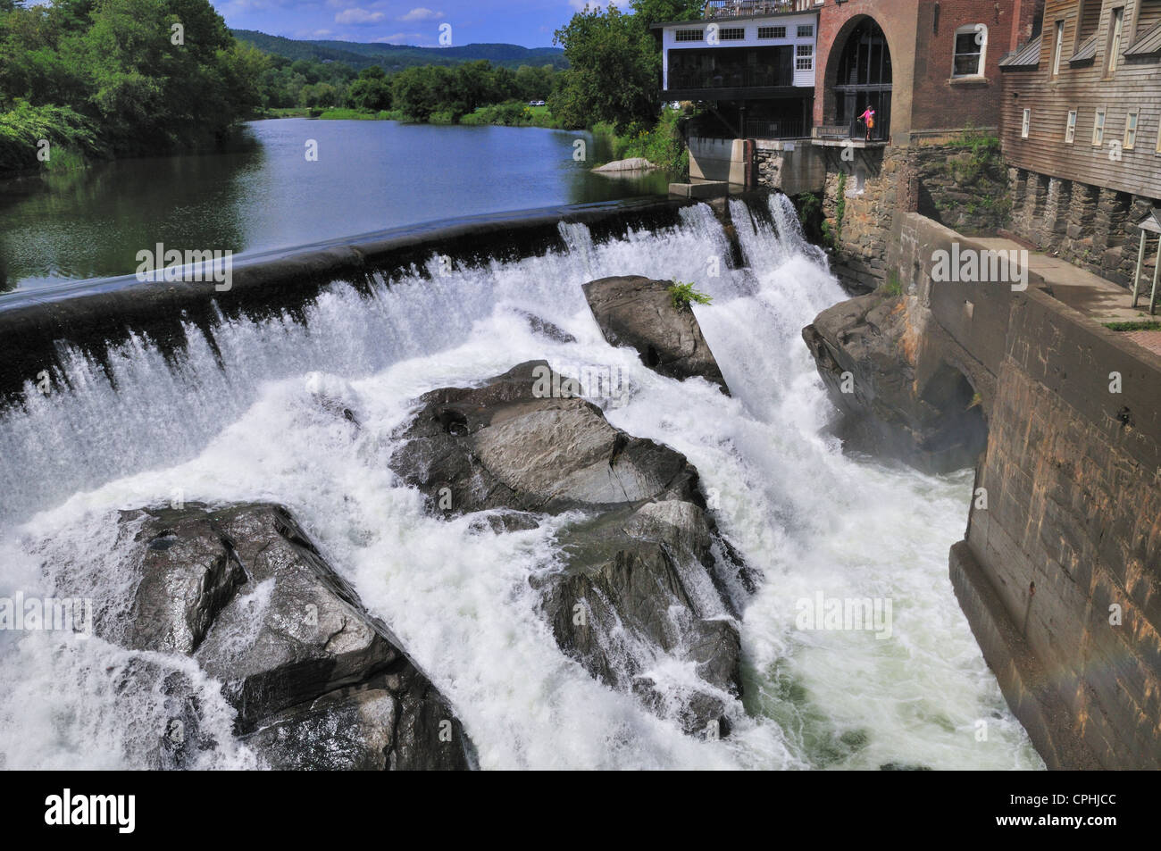 Water races over the Quechee dam and crashes on the boulders downstream - Stock Image