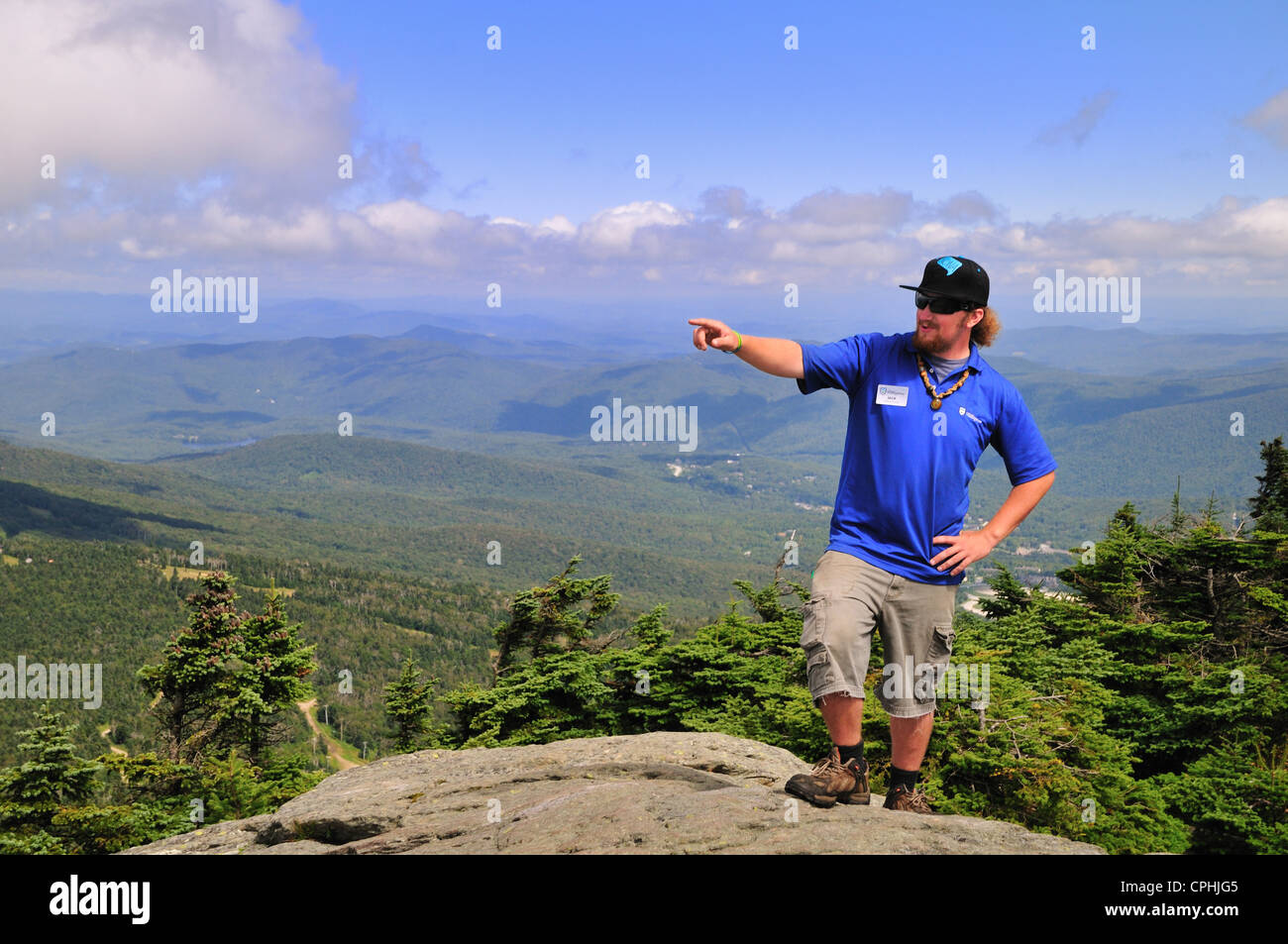A guide atop Killington mountain in central Vermont points out a distant feature - Stock Image
